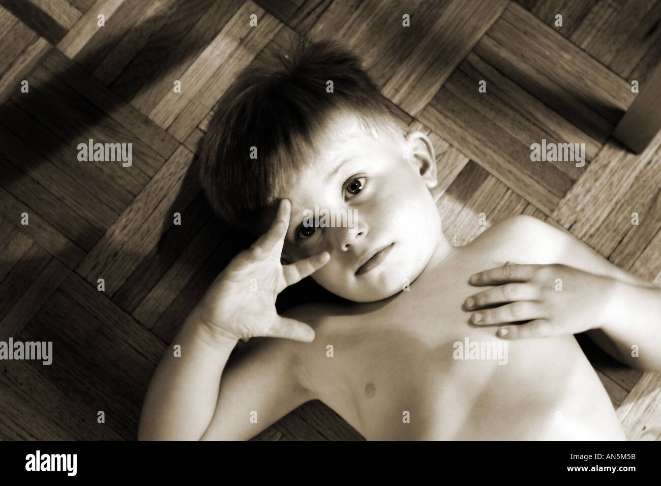 Child looking into camera with serious look, laying on floor looking up. Sepia Toned Black and White. - Stock Image