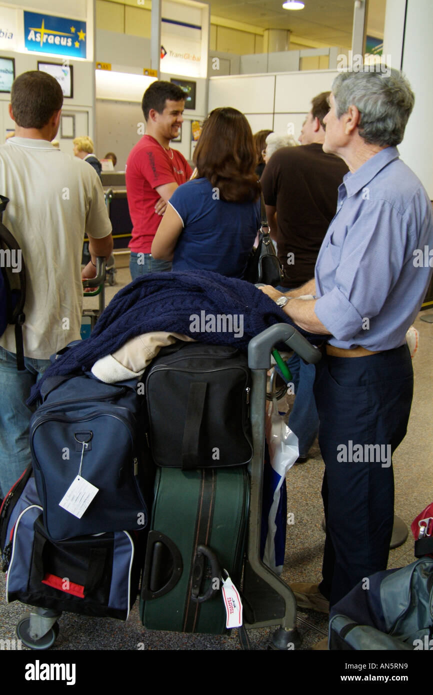 844def1be33a9 Passenger with luggage trolley waiting in check in line. Gatwick Airport  London UK - Stock