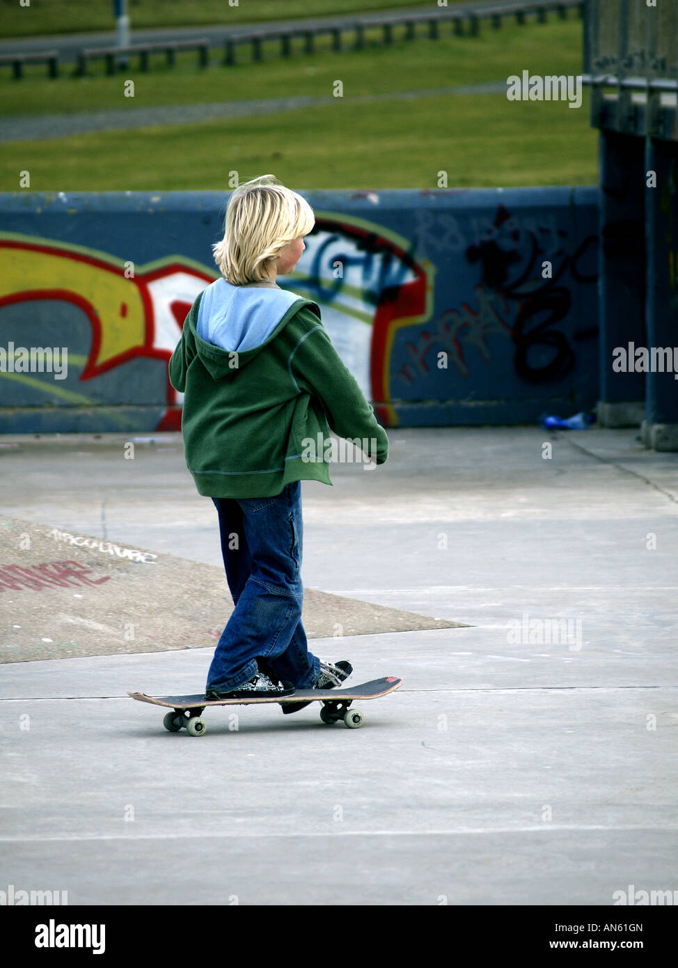 Blonde haired boy on a skateboard in a skate park. - Stock Image