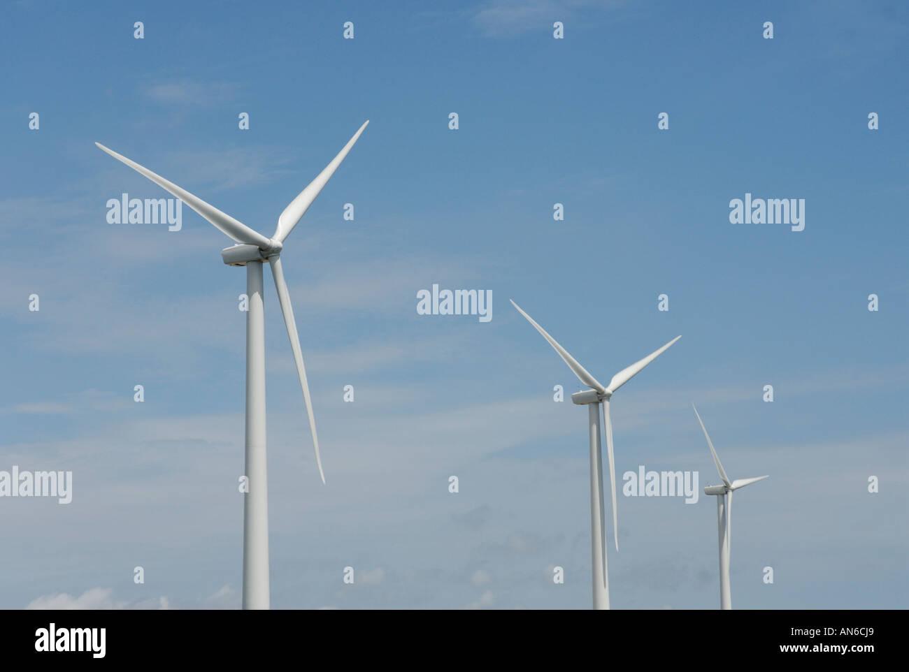 Three wind turbines, close-up of blades, against blue sky. Wind power 'wind farm' turbines alternative energy, - Stock Image