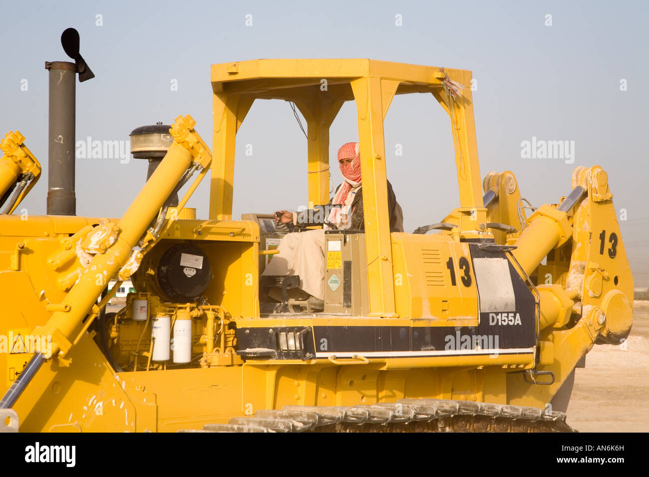 Palestinian headdress protected worker driving a bulldozer on a dusty construction site - Stock Image