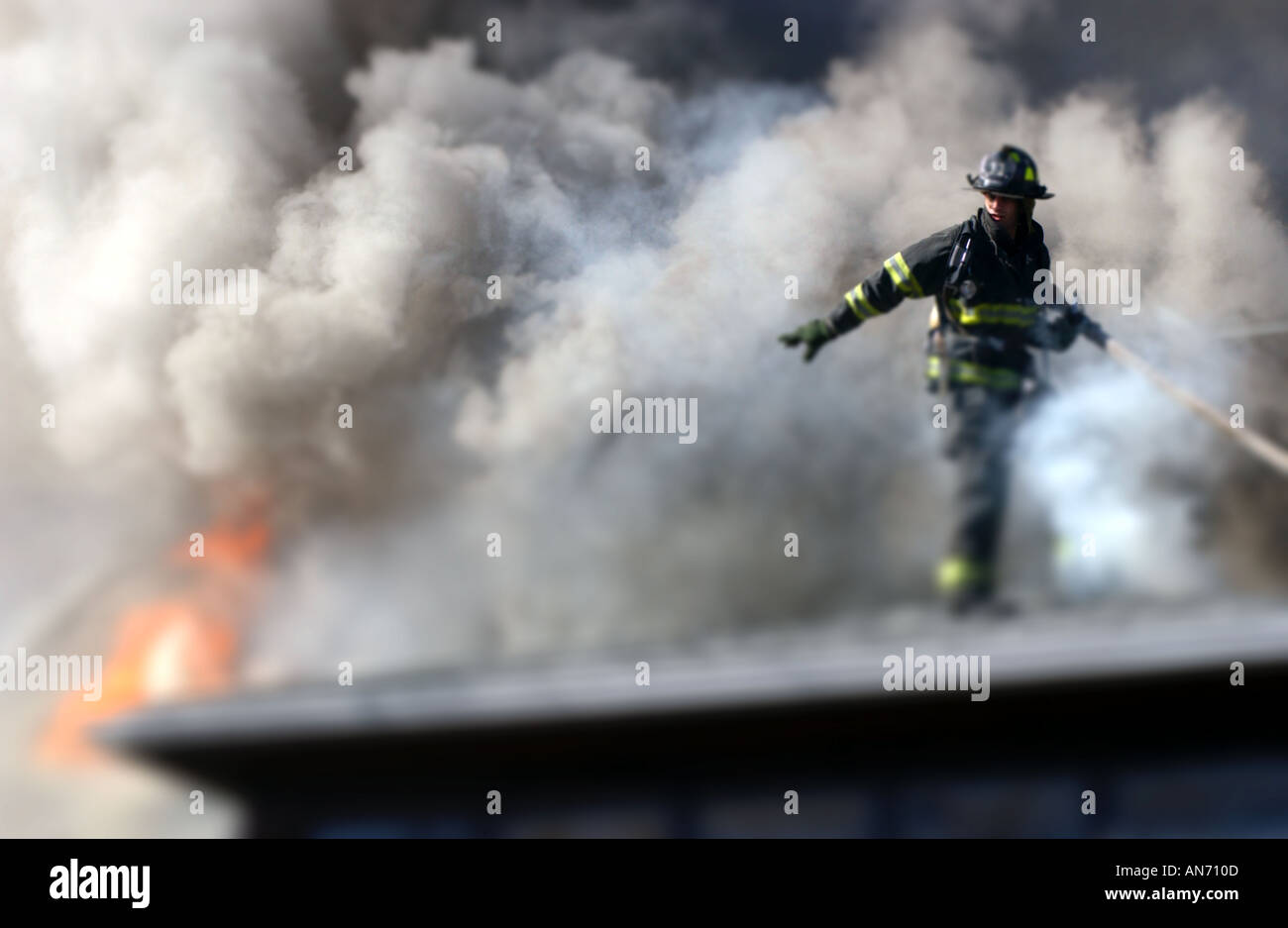 Firefighter on a roof fighting a fire Stock Photo