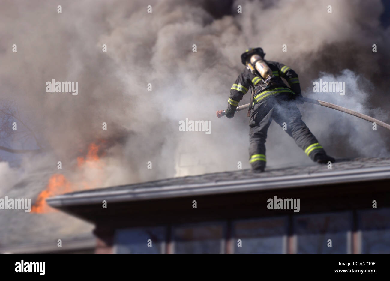 Firefighter on a roof fighting a fire - Stock Image