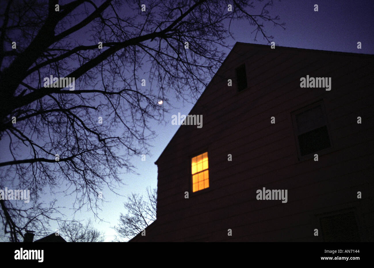 'working late' A house at dusk with a single room lit. insomnia, insomniac. Night. 'night fall' - Stock Image