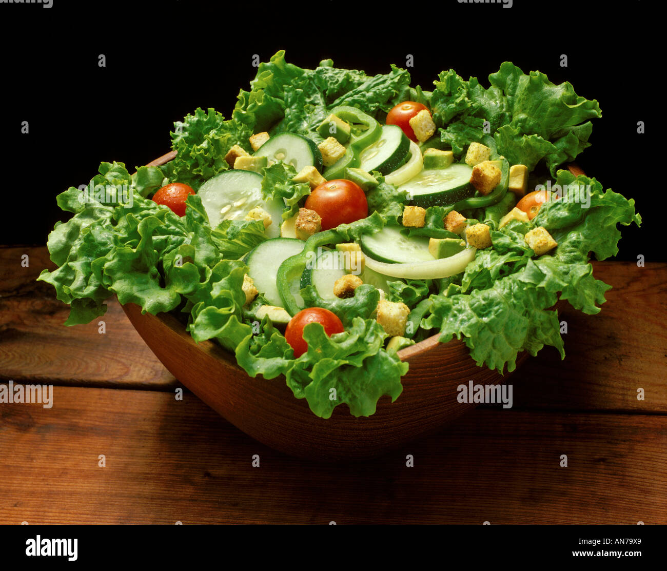large bowl of fresh mixed green salad with vegies on top stock photo