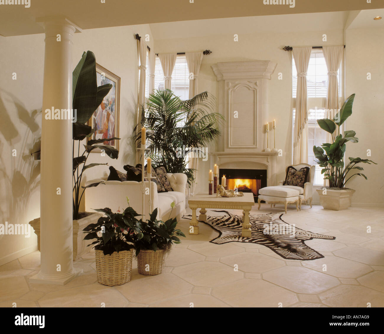 Living Room In White With Gothic Fireplace Tall Plants White Couch