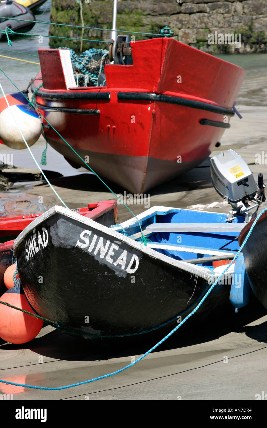 An old style fishing currach named Sinead and a larger red boat both stranded on the sandy bottom Stock Photo