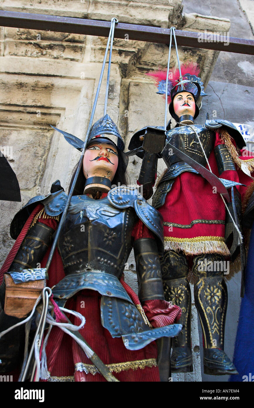 Puppets dressed in military armor and bright red skirts hang as if in warning - Stock Image