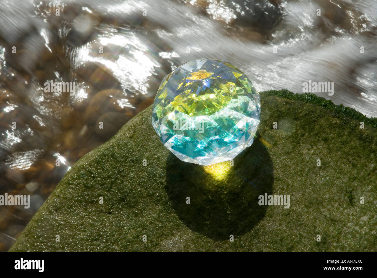crystal cut glass object on pebble beach - Stock Image