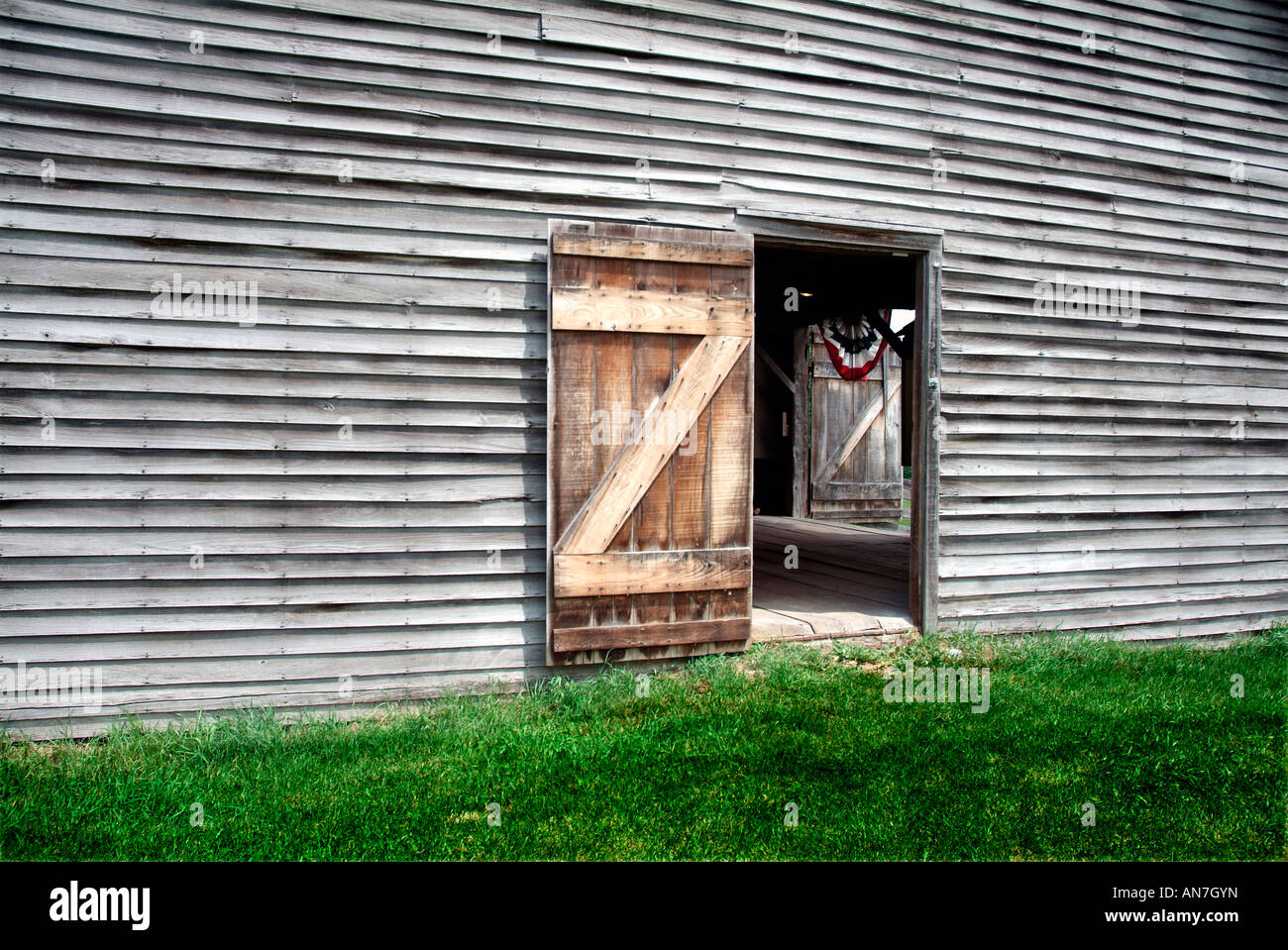 Old weather-beaten barn. A door is open, allowing the viewer to see the red, white & blue bunting hanging in - Stock Image