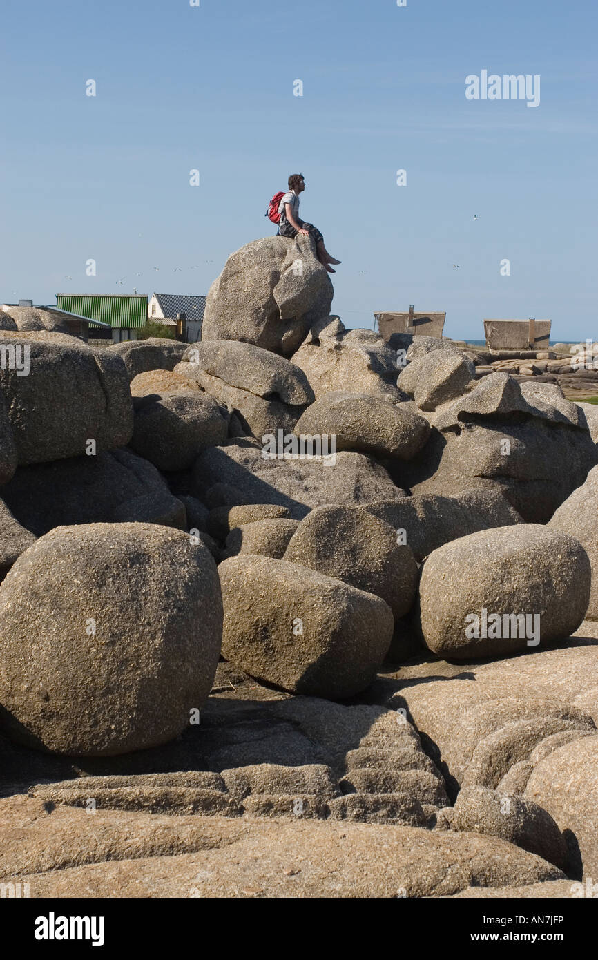 Man Sitting on Rocky Beach - Stock Image