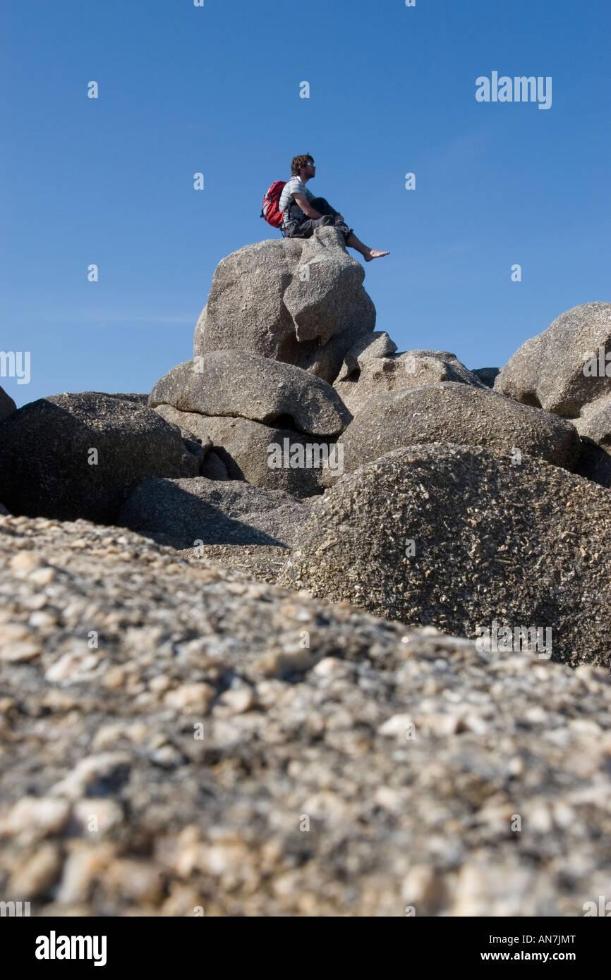 Male Sitting on Rock - Stock Image