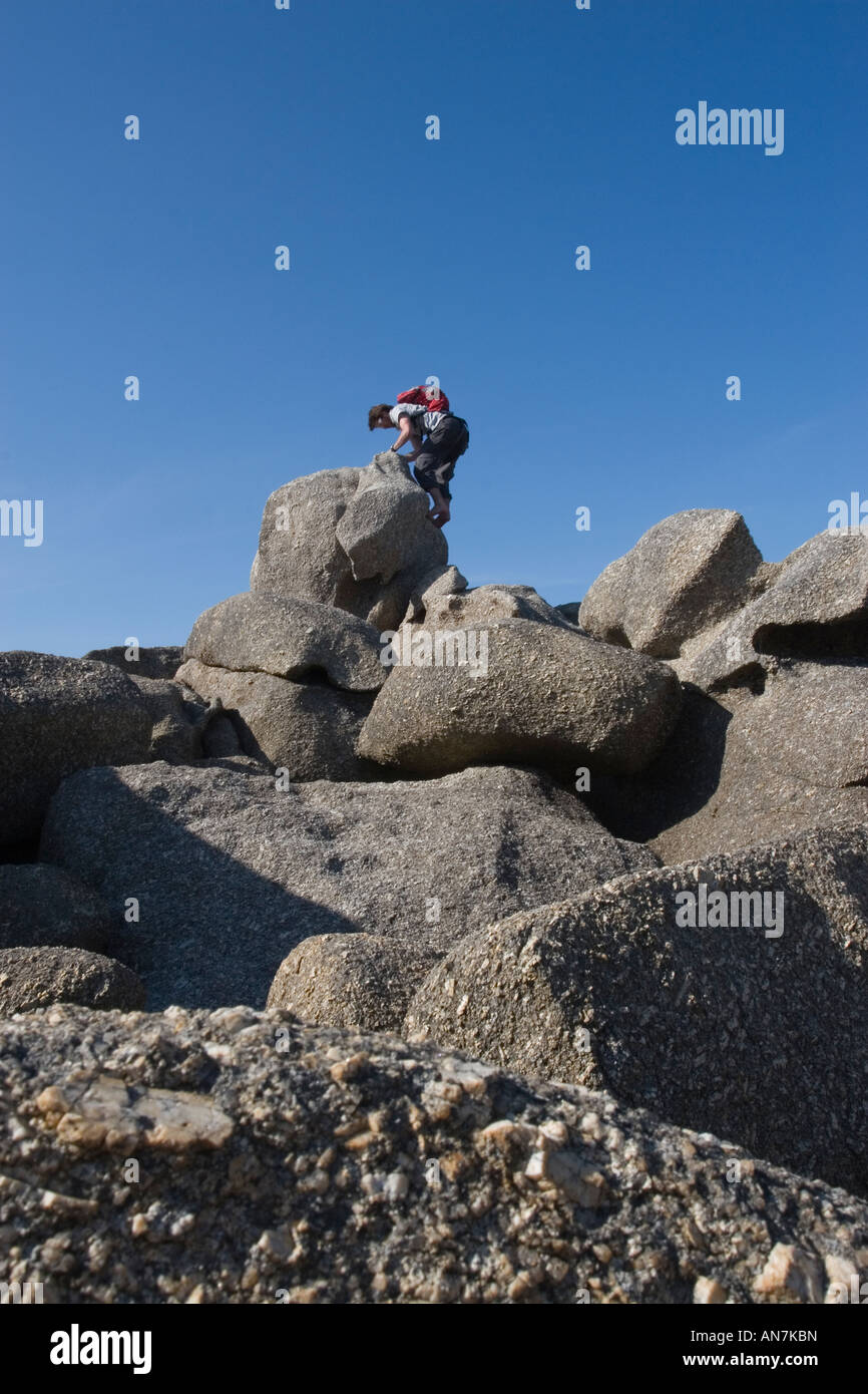 Man Scrambing Up Rock on Beach - Stock Image