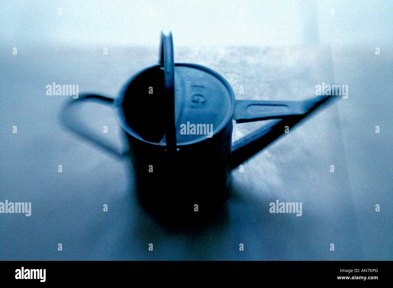 traditional galvanised steel watering can blue tone and blurry holds 1 gallon - Stock Image