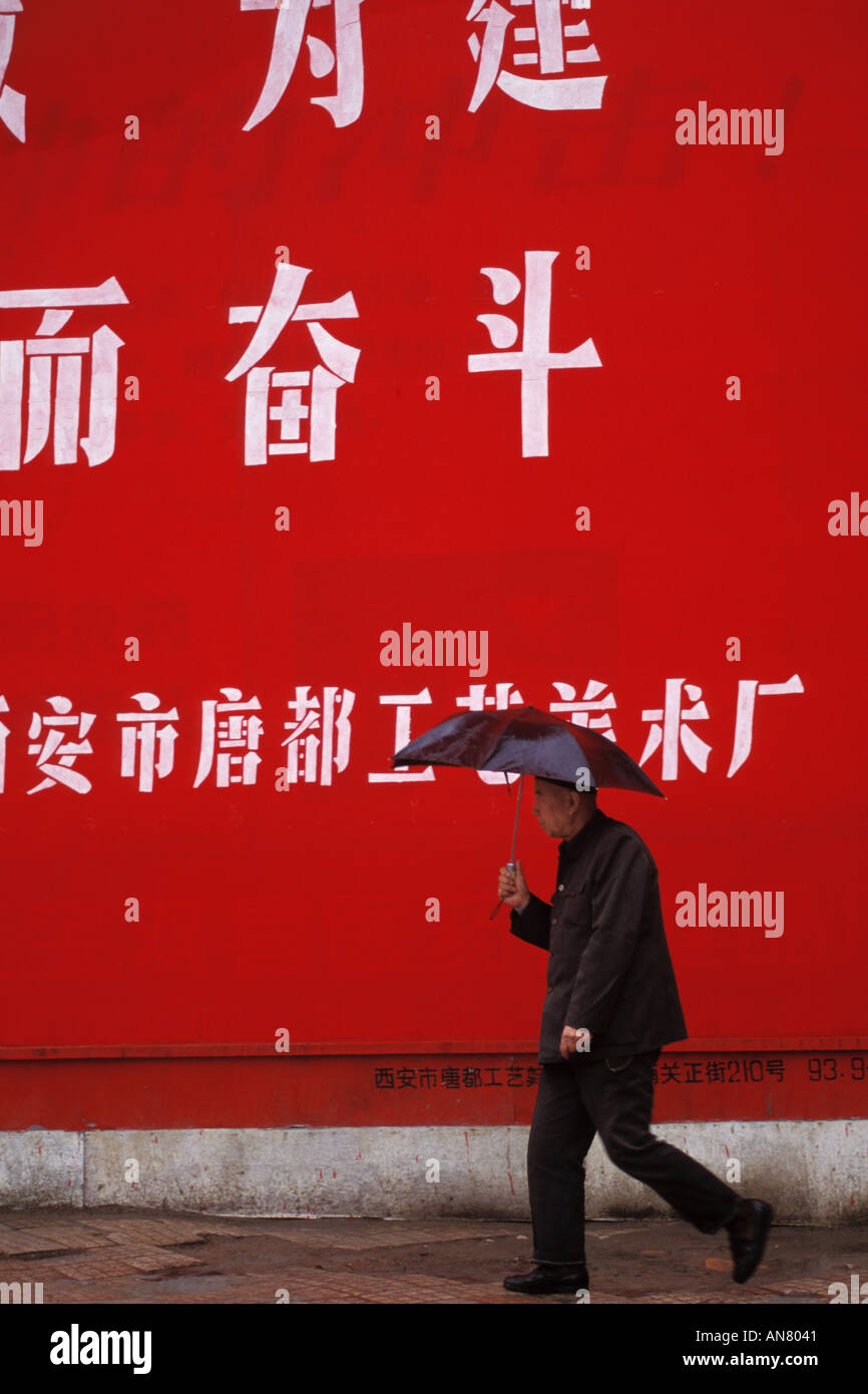China, Xian, Street scene, man with umbrella - Stock Image