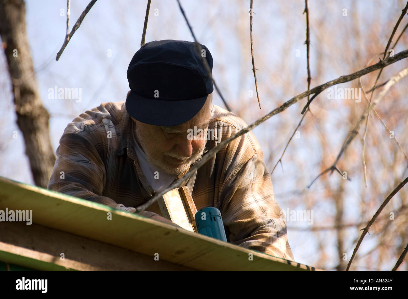 senior in a ladder framing the roof an hunter shack - Stock Image