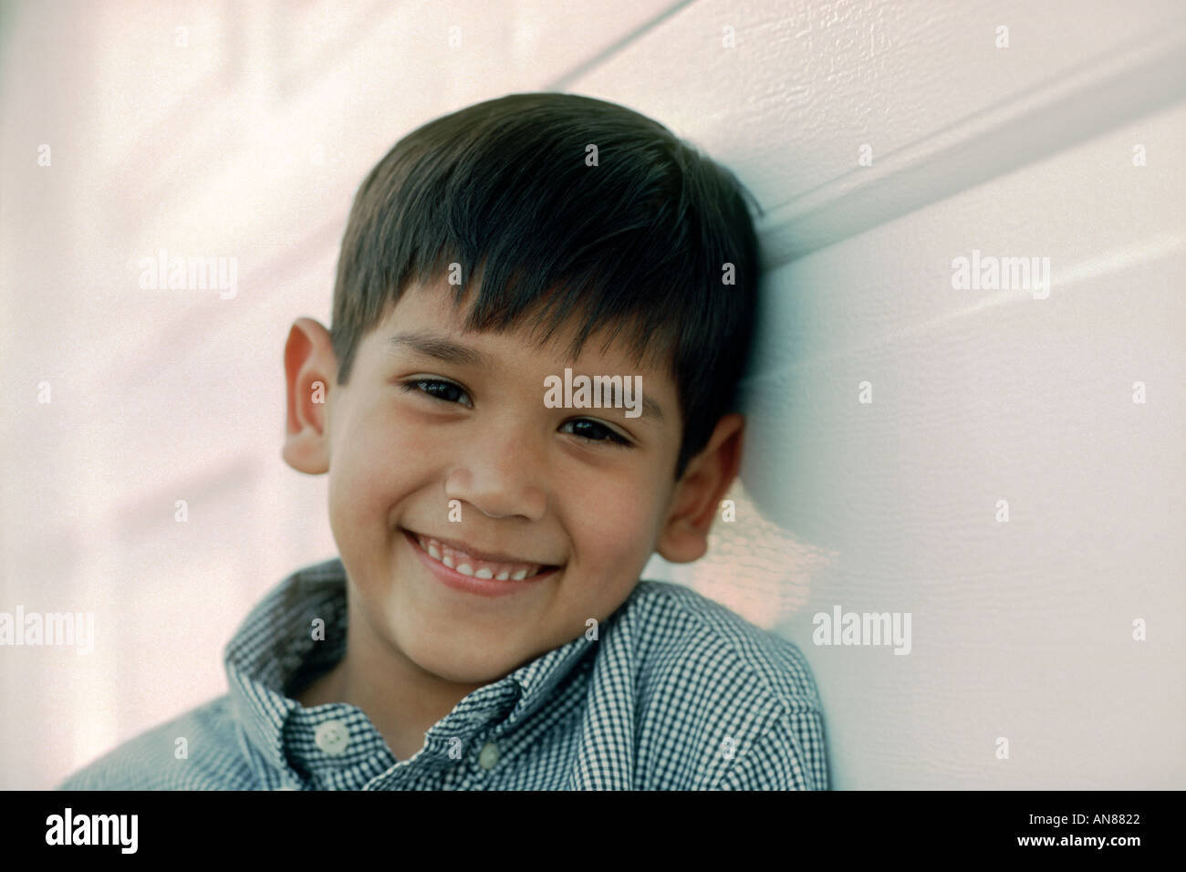 Portrait of 6 year old Mexican American leaning against white wall - Stock Image
