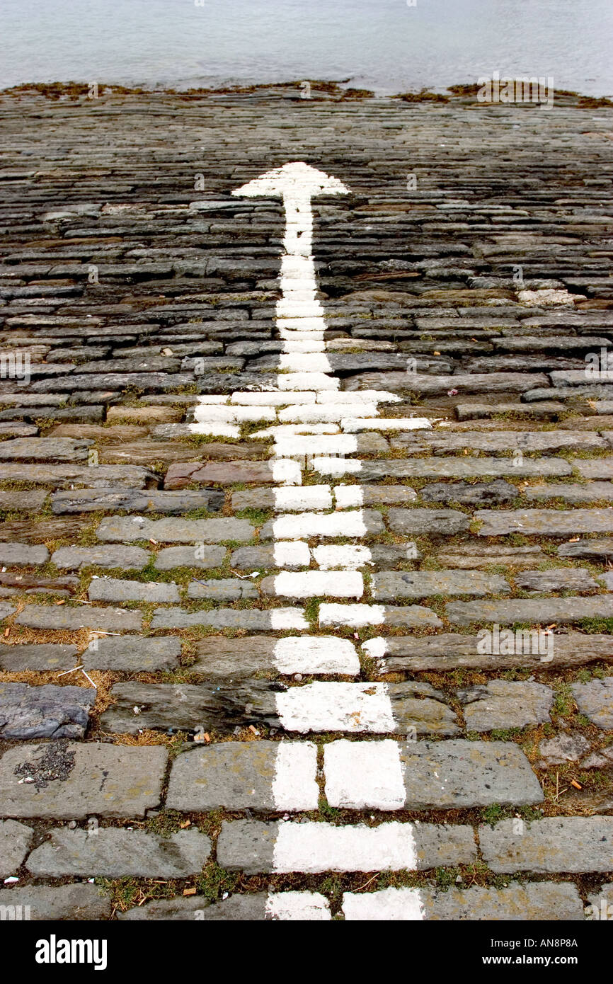 Directional signs paint on rock floor paved outdoor with arrows pointing in opposite directions to the sea Stock Photo