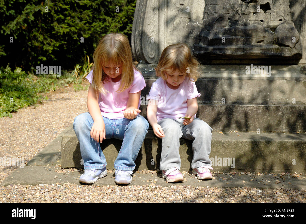 Two girls sitting on statue step. Stock Photo