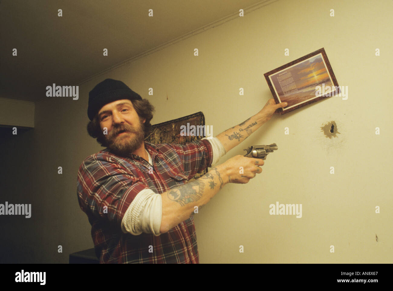 Man with gun showing bullet hole he put in wall Portsmouth New Hampshire - Stock Image