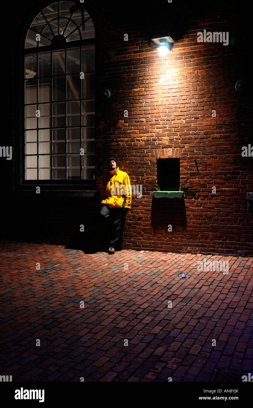 Man leaning on a brick wall under a streetlight on a cold winter night Distillery District Toronto - Stock Image