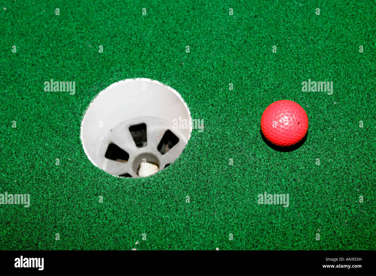 golf ball by hole artificial grass green putting green at night with harsh on camera flash - Stock Image