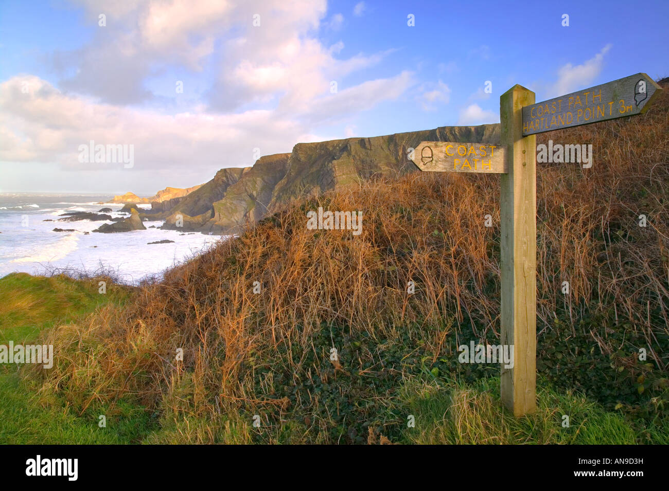 Signpost for the South West Coast Path at Hartland Devon England with views of the cliffs Stock Photo