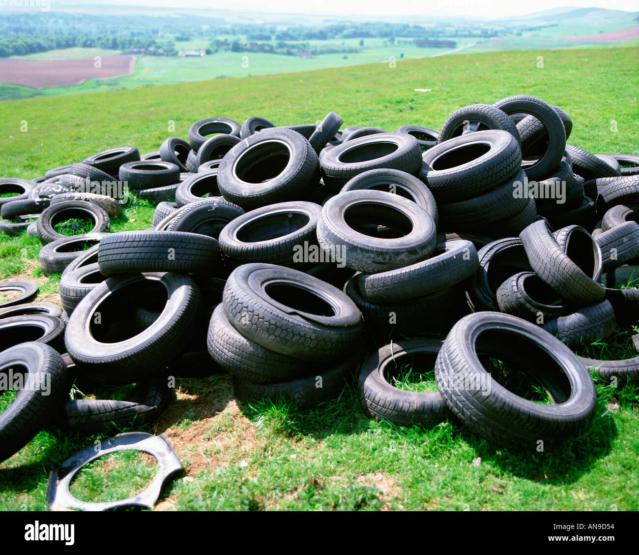 Tyres dumped in countryside - Stock Image