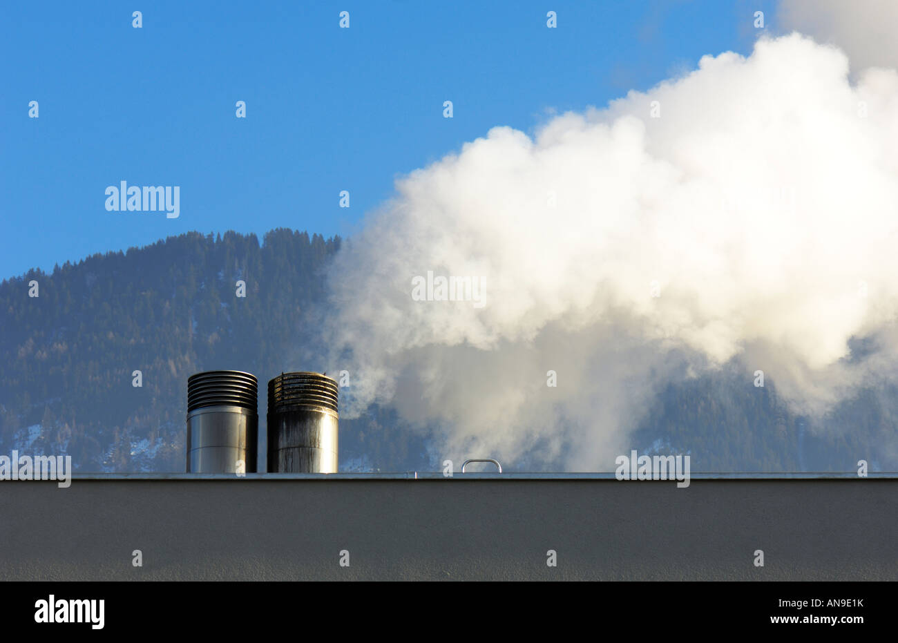 Two chimneys and white smoke - Stock Image