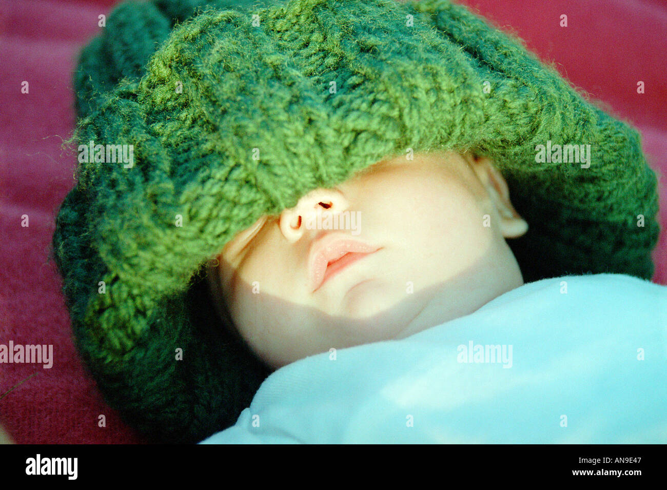 Baby in oversize wool hat - Stock Image