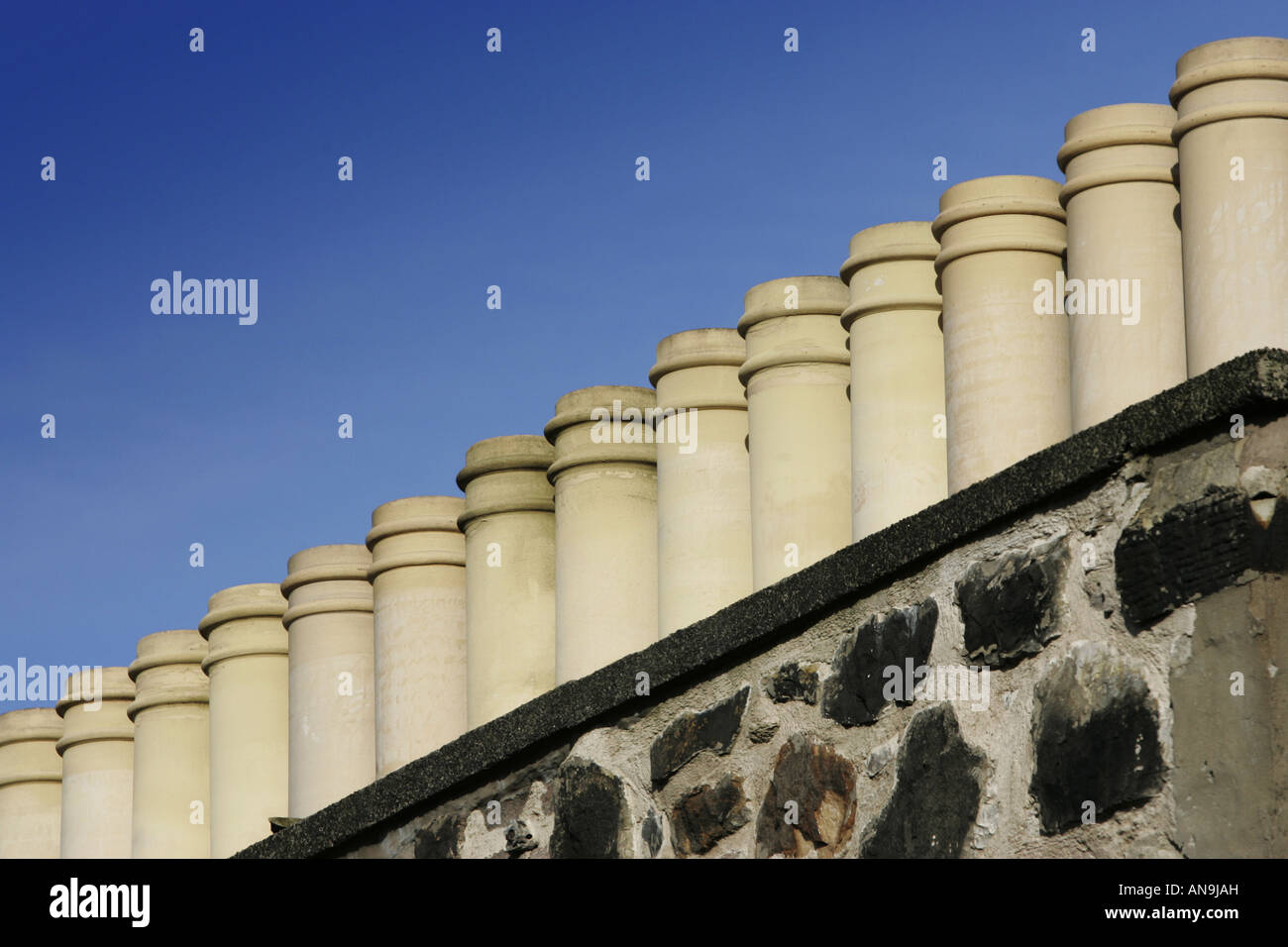 A row of chimney pots composed diagonally against a blue sky. - Stock Image