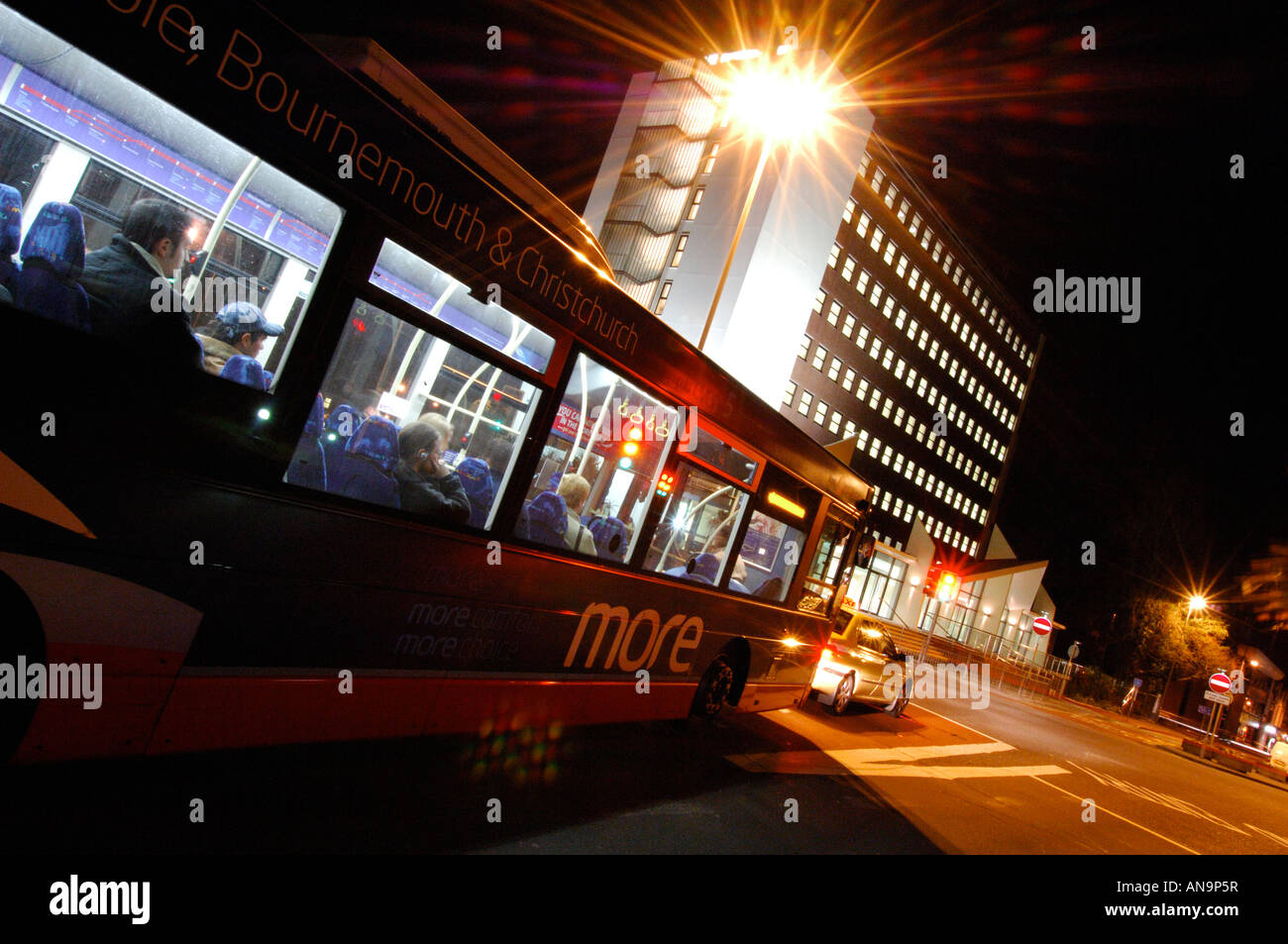 an office block at night with traffic light trails illuminated in a city or urban nightlife environment. - Stock Image
