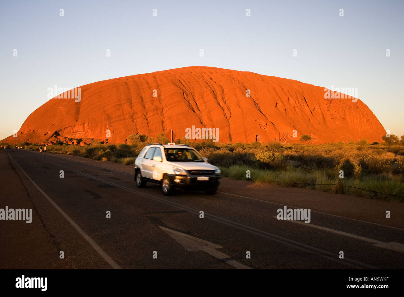 Car drives past Ayers Rock Uluru Red Centre Australia Stock Photo