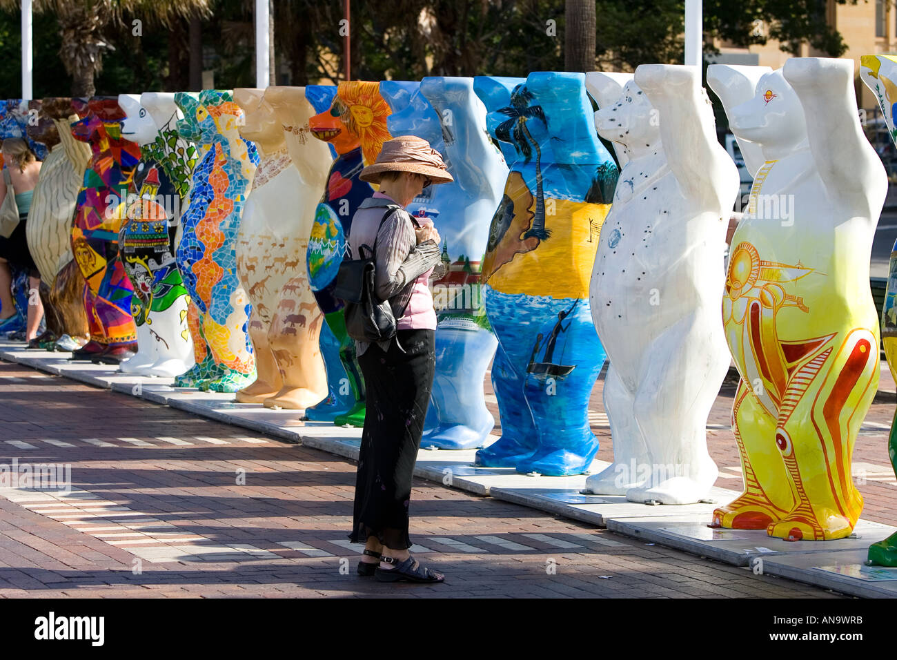 Tourist admires the Unicef charity fundraising United Buddy Bears in Sydney New South Wales Australia Stock Photo