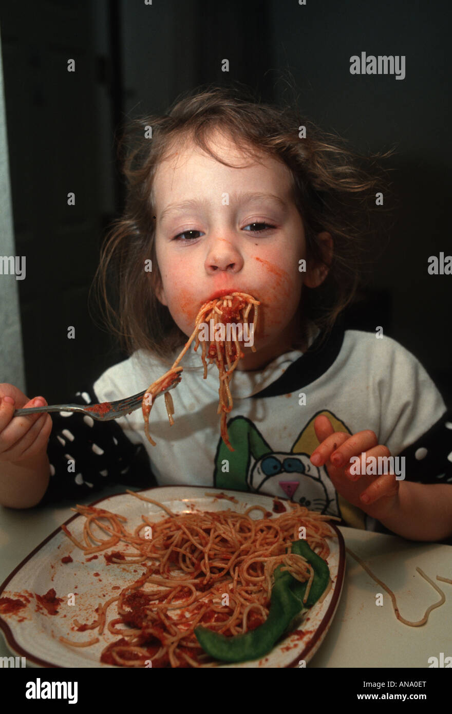 Little girl really digging into her spaghetti - Stock Image
