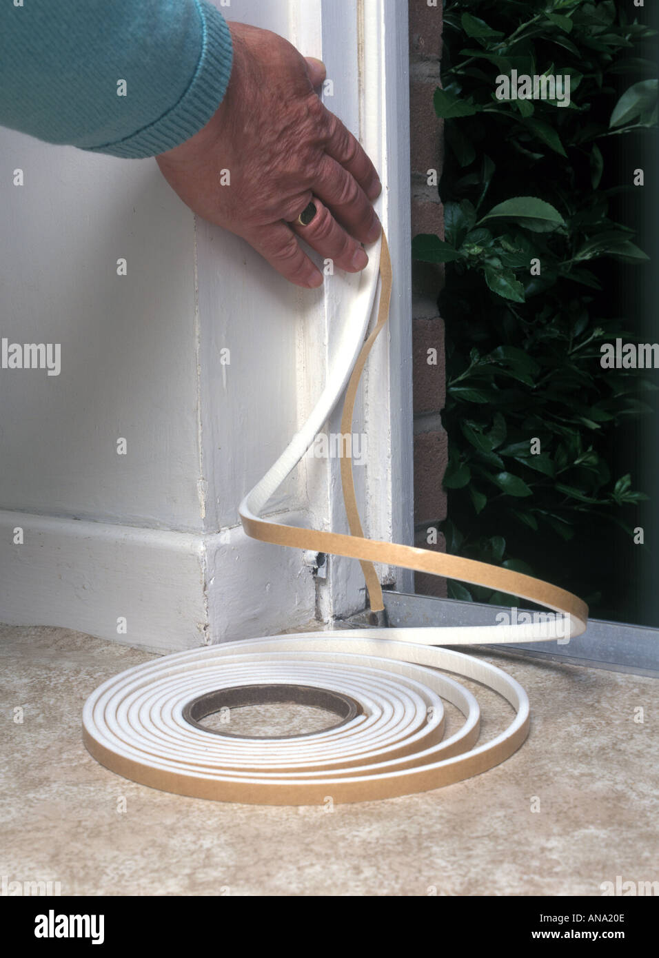 fitting self adhesive PVC foam draught excluder round a door opening to save heat - Stock Image