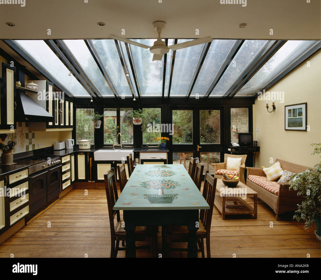 Decoratively Painted Table And Comfy Sofa In Modern Openplan Kitchen Dining Room Extension With Glass Roof