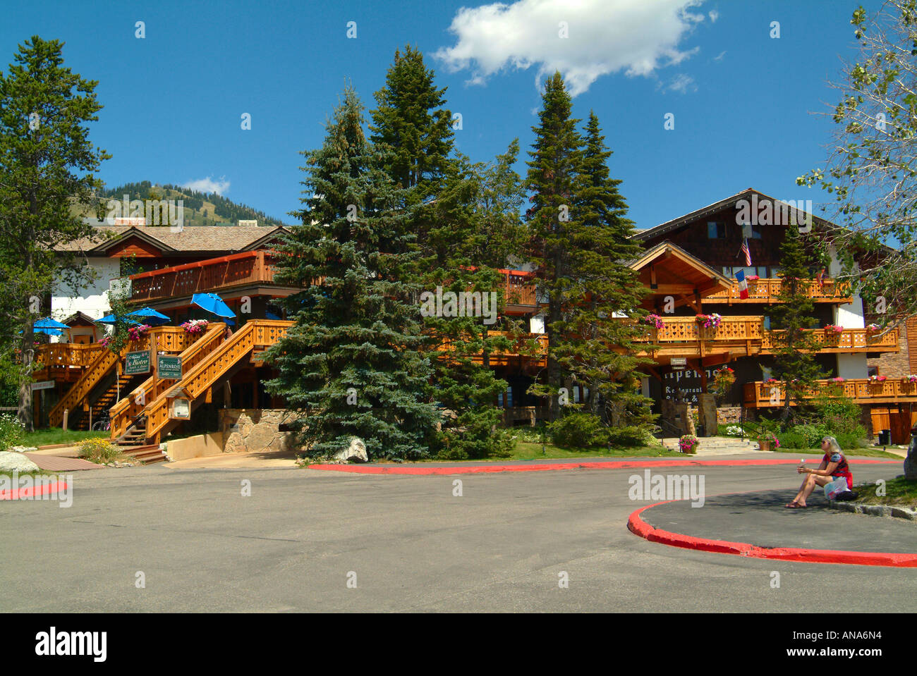 Young Woman Sits Outside The Balconied Chalet Style Alpenhof Hotel in Teton Village near Grand Teton National Park Stock Photo