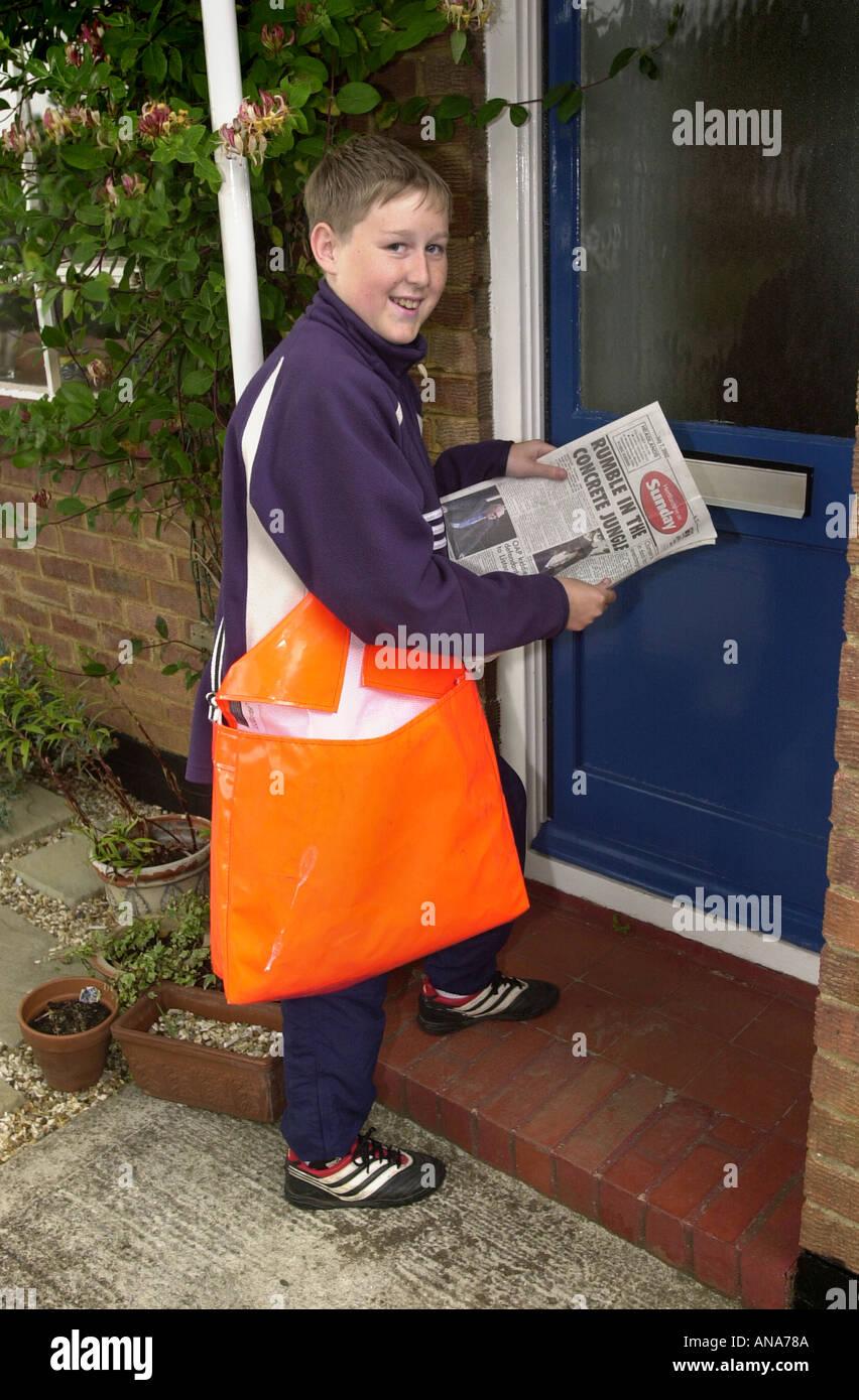 Boy delivering newspapers UK - Stock Image