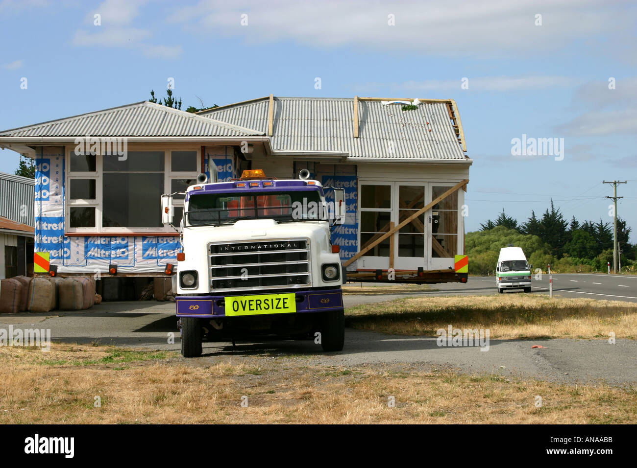 Moving oversize house on truck in New Zealand campervan in background Stock Photo