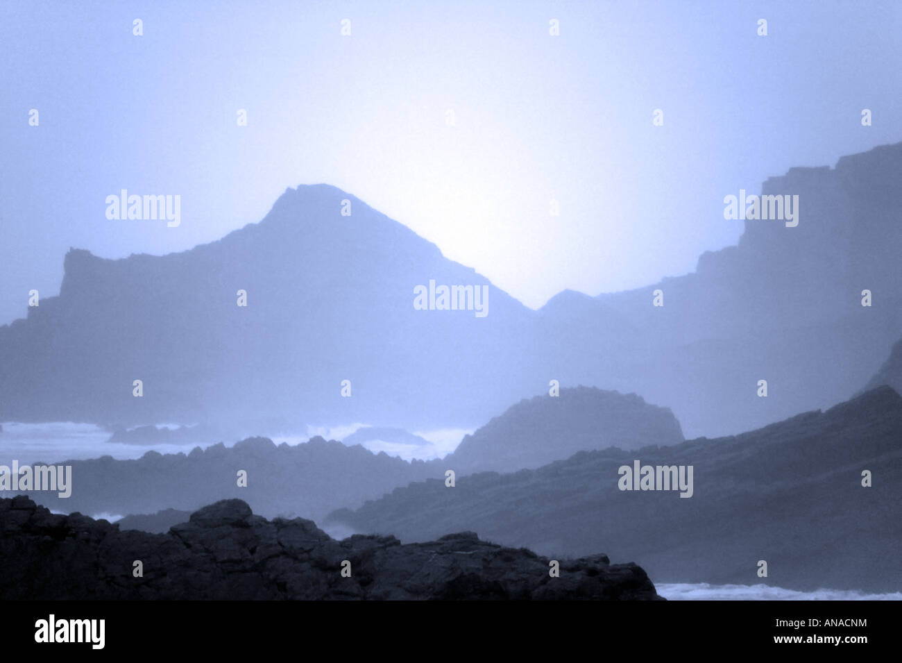 Sea fog on a rocky coastline grainy image as a result of natural light conditions - Stock Image