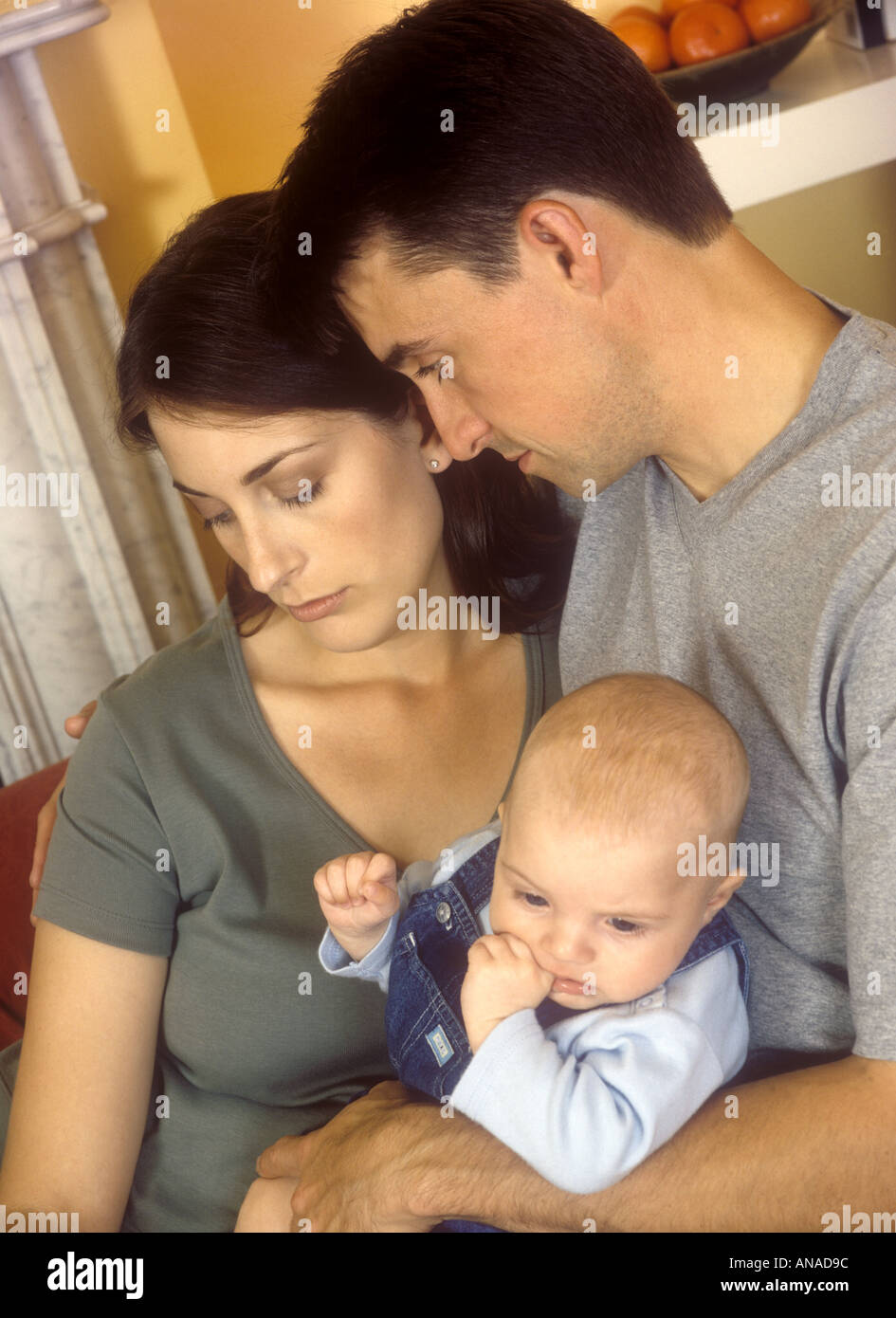 Mother with postnatal depression being comforted by her husband - Stock Image