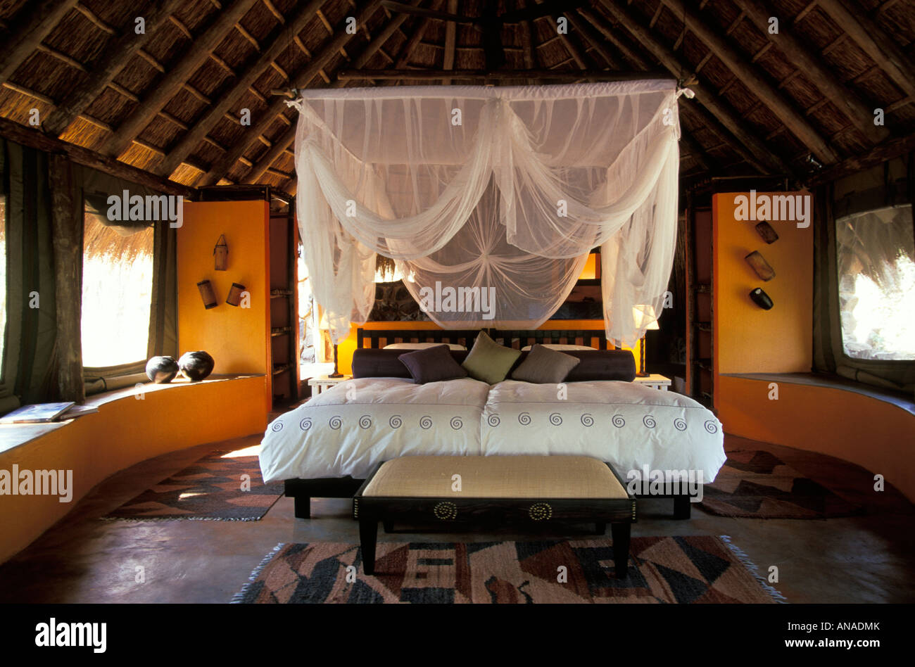One of the bedrooms at Jaci's Lodge, furnished with a four poster canopy bed with a draped mosquito net - Stock Image
