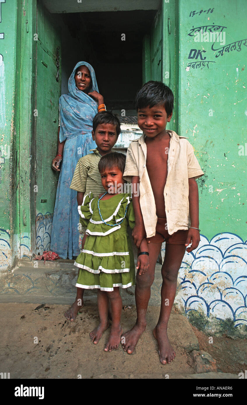 Friendly children and mother from Khajuraho in the state of Madhya Pradesh standing at the door to their rural home India - Stock Image