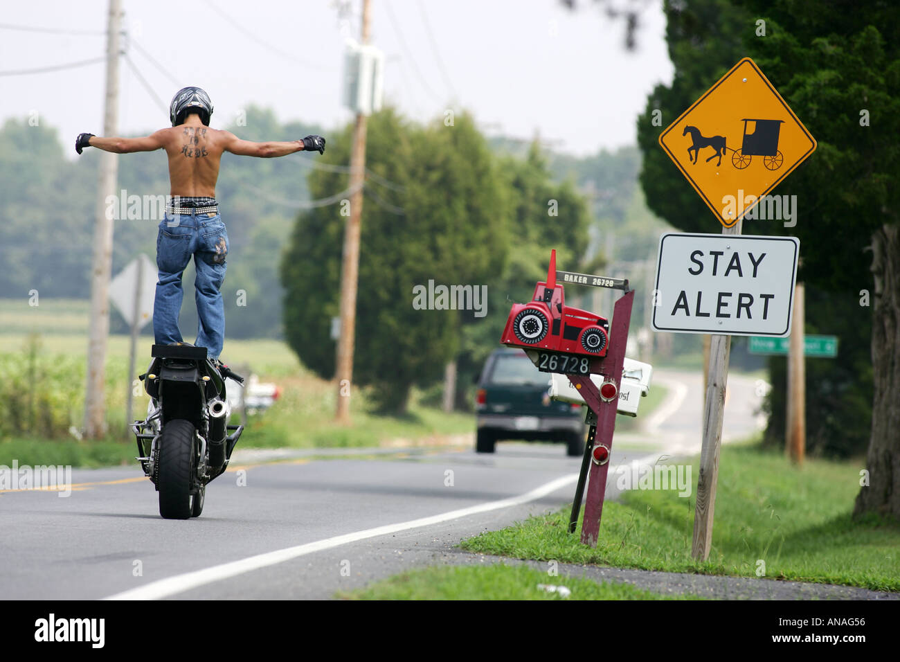 Motorcycles doing stunts including wheelies and jesus christs and burnouts - Stock Image