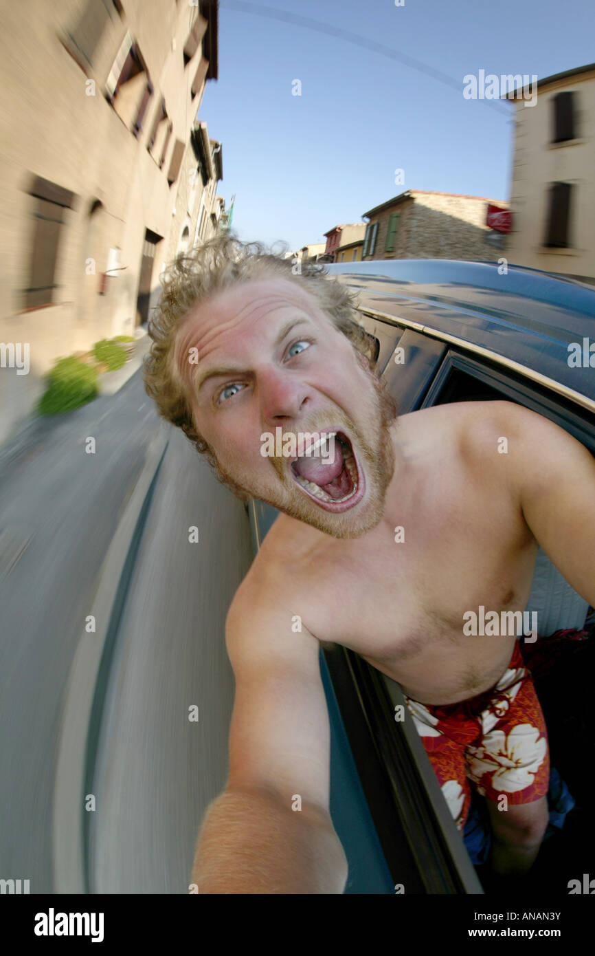 young fair-haired man making a selfportrait in a driving car - Stock Image