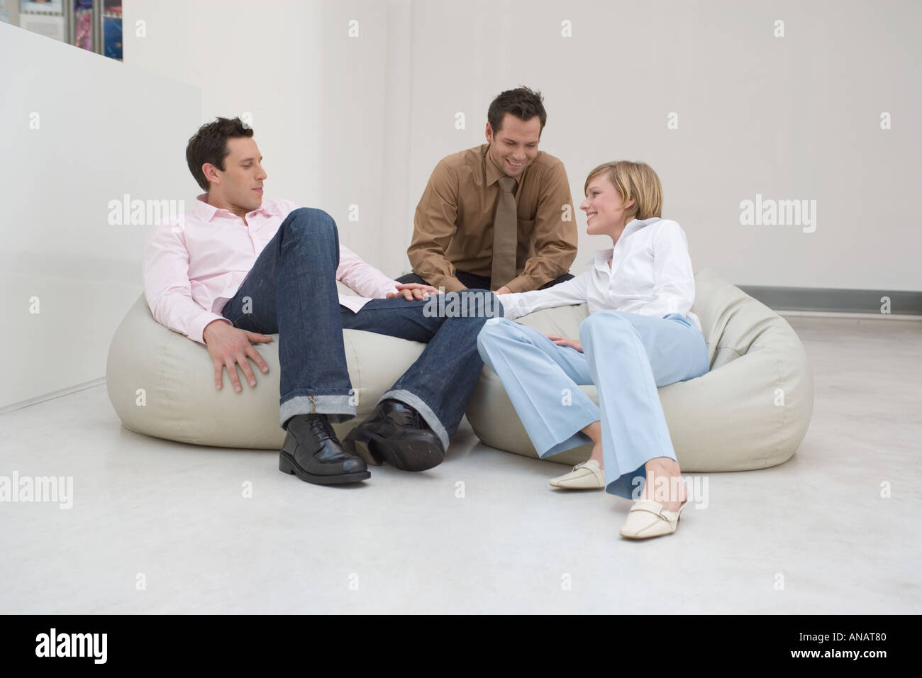 three people sitting on bean bags having a conversation in relaxed office area - Stock Image