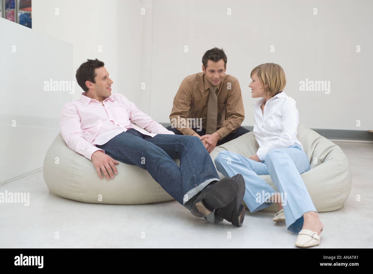three people relaxing on bean bags and talking - Stock Image