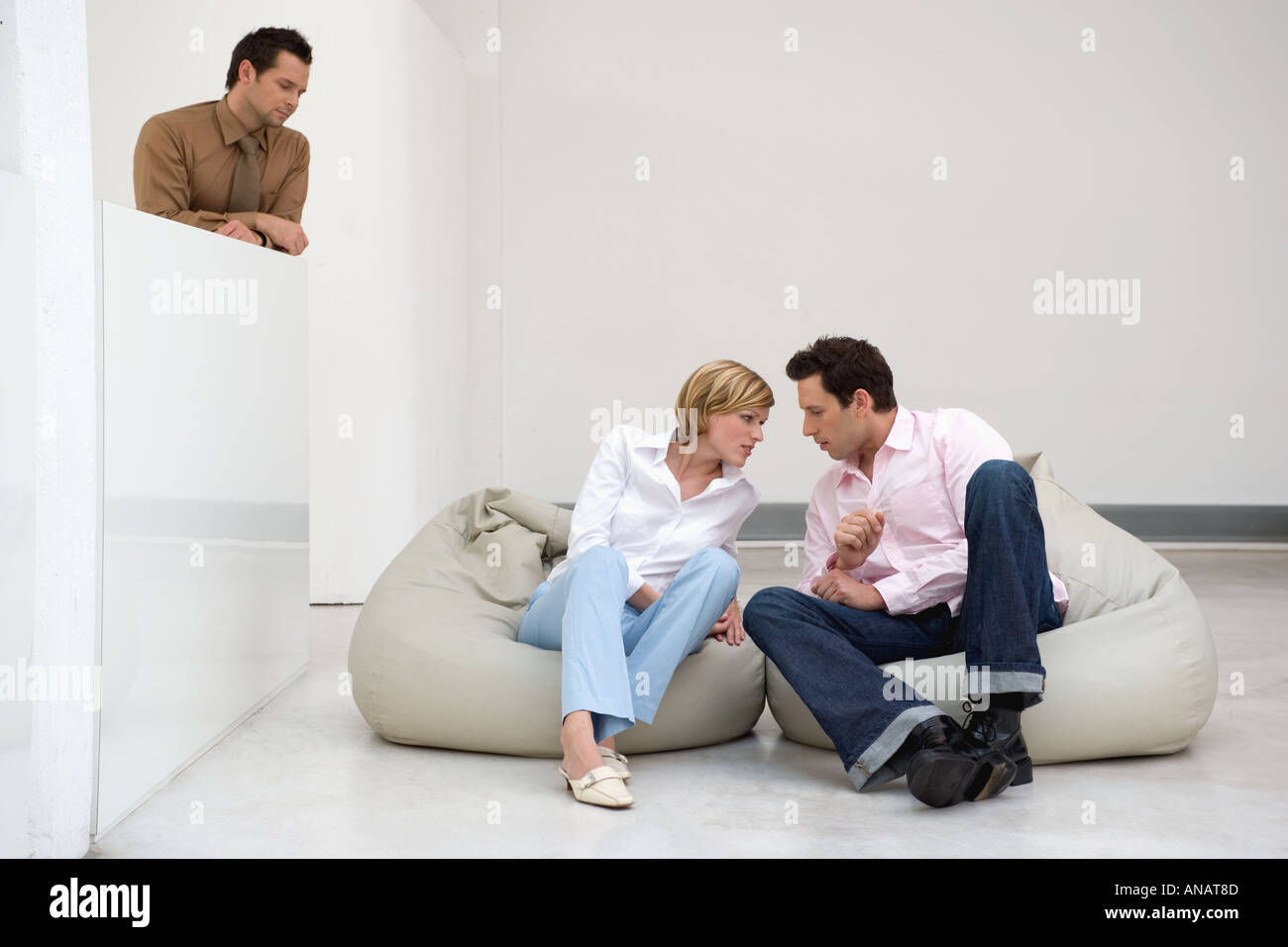 man and woman whispering to each other as another man watches and listens - Stock Image