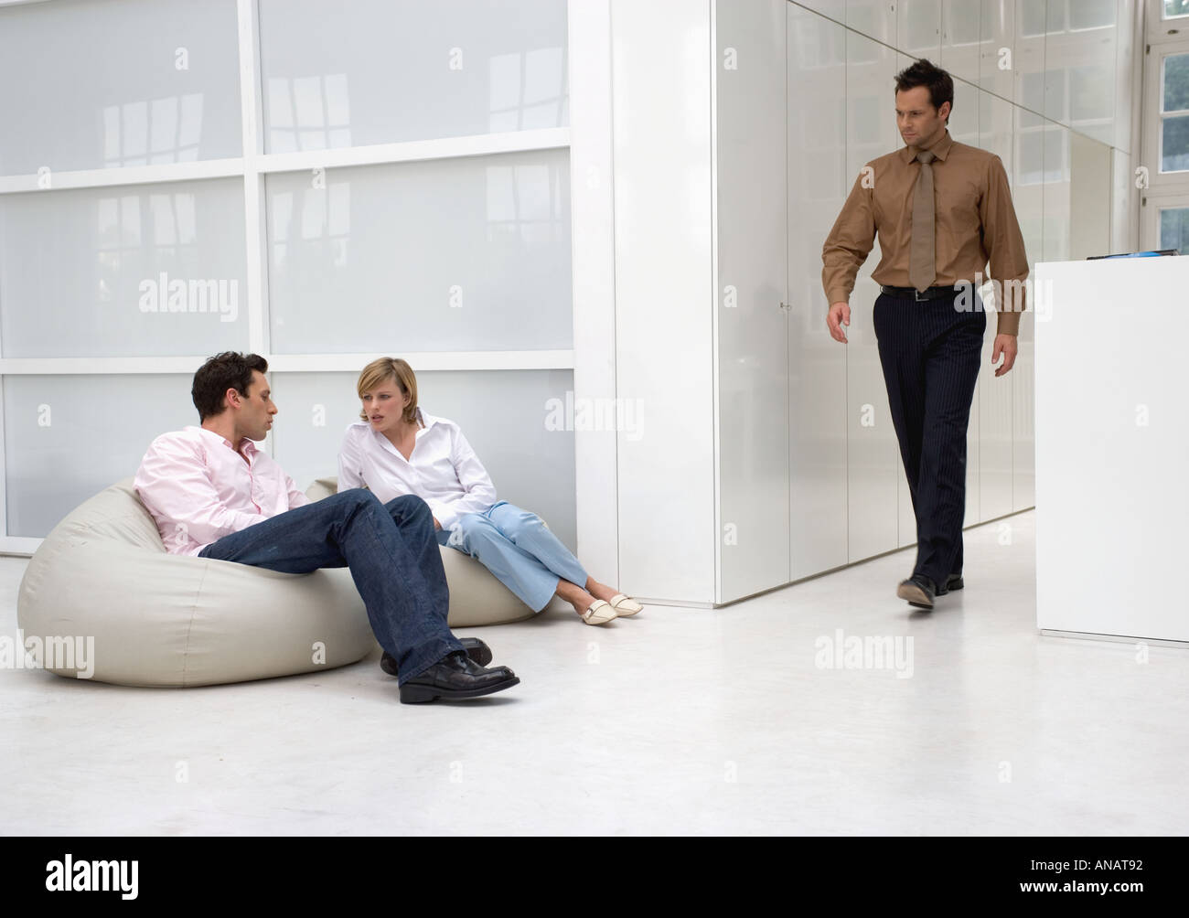 businessman and businesswoman talking to each other in casual office area as another man walks along - Stock Image
